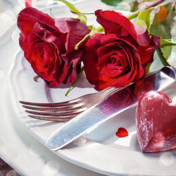 Festlich gedeckter Tisch beim Catering mit roten Rosen und Herz